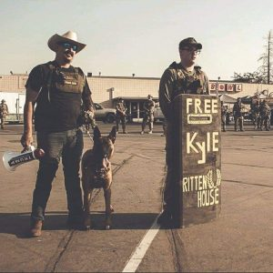 "Christopher Young (left) next to a homemade shield that says ""Free Kyle Rittenhouse"" next to the Proud Boys logo in Atwater, CA"